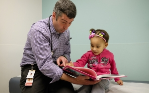 At PhilaKIDS at St. Christopher's, Dan Taylor, D.O., eases the experience for a young patient by making her smile